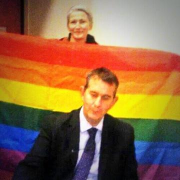 Northern Ireland's Health Minister, Edwin Poots (DUP) in front of a rainbow flag, held by LGBT rights advocate, Sha Gillespie.