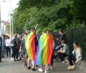 Two people wrappted in rainbow flags