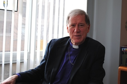 Archbishop Fred Hiltz, grey haired man sitting in priest's clothes