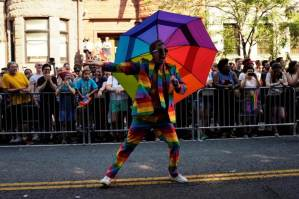 man with rainbow umbrella at pride parade